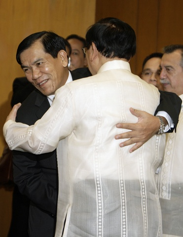 Myanmar's Foreign Minister U Nyan Win hugs his counterpart Alberto Romulo during a bilateral meeting in Manila