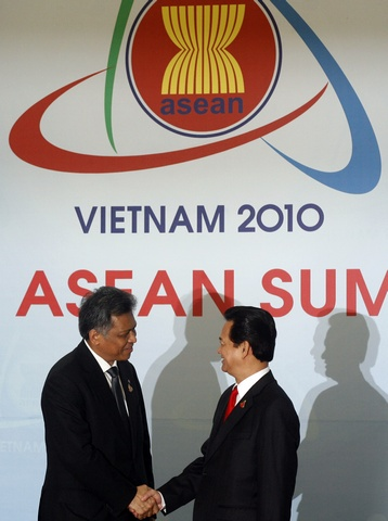 ASEAN Secretary-General Surin Pitsuwan is greeted by Vietnam's Prime Minister Nguyen Tan Dung before the 16th ASEAN Summit in Hanoi