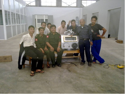 A group of Burmese military and civilian workers pose with a glove box they built at Factory 1 near Pyin Oo Lwin
