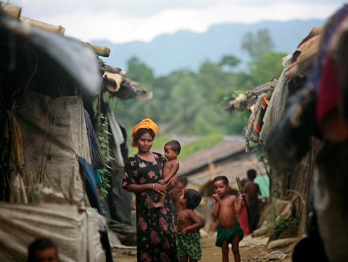 A Rohingya refugee from Burma stands with her child in front of makeshift huts in a Cox's Bazaar refugee camp, with the mountains of Burma in the background. 2009. (PHOTO: Reuters)