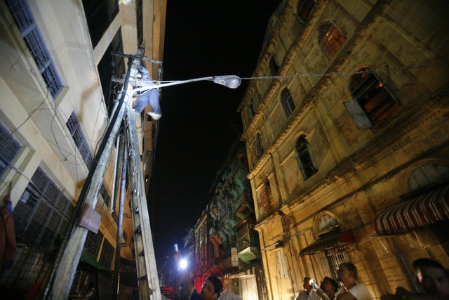 In this file photo, Rangoon residents try to restore electricity supply to their neighbourhood during a blackout. (PHOTO: Reuters)