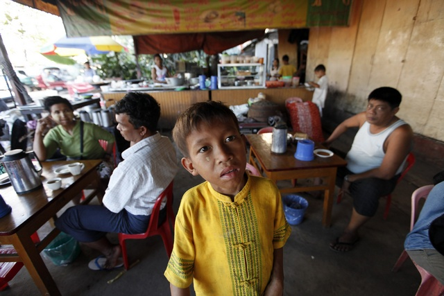 A child beggar asks for money in a tea shop in Rangoon. (PHOTO: REUTERS/Soe Zeya Tun)