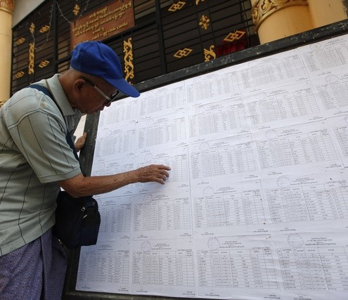 A man searches for his name through lists of voters outside an election commission office in Yangon