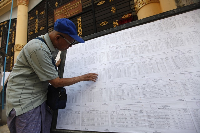 A man searches for his name through lists of voters outside an election commission office in Rangoon on November 4, 2010. (Reuters)