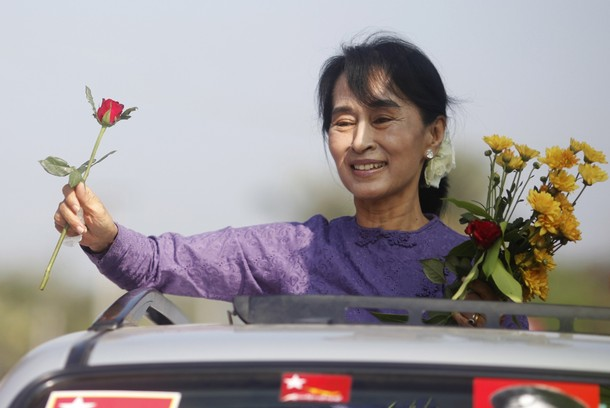 Aung San Suu Kyi holds flowers given by supporters as she stands on a vehicle en-route to Kawhmu township, the constituency where she will contest April by-elections (Reuters)