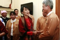 Burma's opposition leader Aung San Suu Kyi (C) shakes hands with a parliament representative  in Naypyidaw in March 2012. (PHOTO: REUTERS)