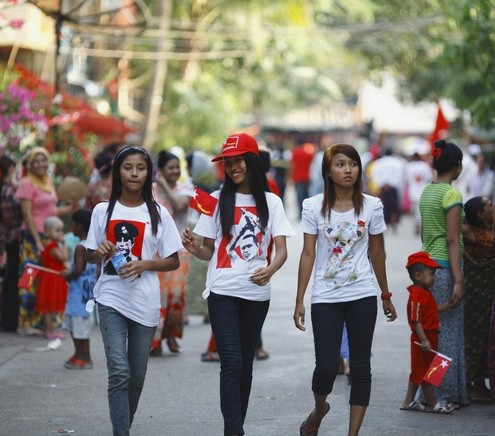 Women wear t-shirts printed with Myanmar's independence hero General Aung San as they walk on a street during an election campaign of the National League for Democracy (NLD) party in Yangon
