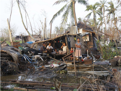 Family members sit near their home destroyed by Cyclone Nargis in Bogalay, Burma in 2008. (Reuters)
