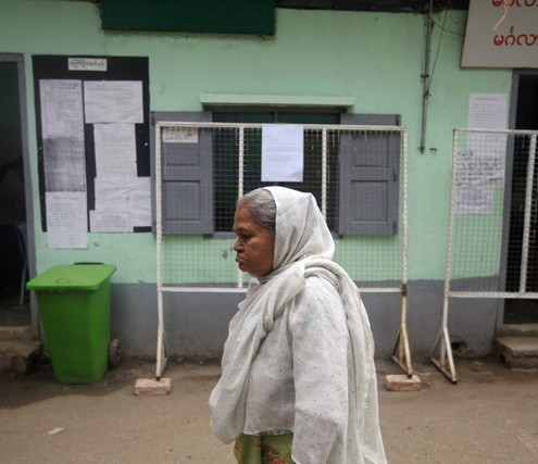 An elderly woman passes by in front of a polling station set up for advanced voting in central Yangon