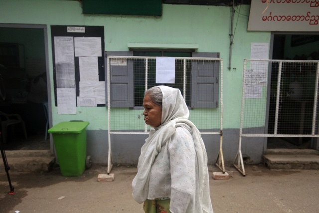 An elderly woman passes in front of a polling station set up for advanced voting in central Rangoon on 31 March 2012. (Reuters)
