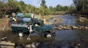A man leaps onto a truck as it forges a creek in a rural part of Myanmar's Kachin state