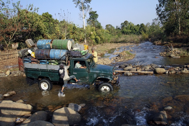A man leaps onto a truck as it forges a creek in a rural part of Burma's Kachin state in February 2012. (Reuters)