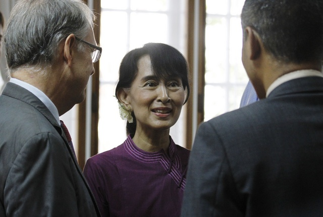 Aung San Suu Kyi talks with guests during the opening ceremony of the EU Office in Rangoon on 28 April 2012. (Reuters)