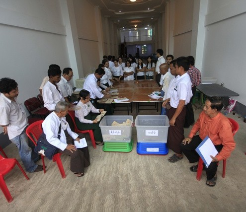 People count votes in a ballot station during by-elections in Yangon