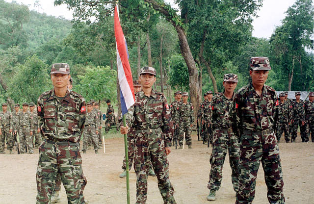 Rebel soldiers of the Karenni National Progressive Party stand to attention with their flag at their jungle base in Burma (Reuters)