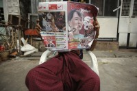 A man reads the newspaper outside his home near the ballot station during the by-elections in Rangoon on 1 April 2012. (Reuters)