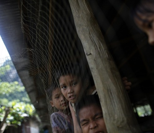 Myanmar's ethnic Karen children look from inside their school at the Mae La refugee camp outside Mae Sot