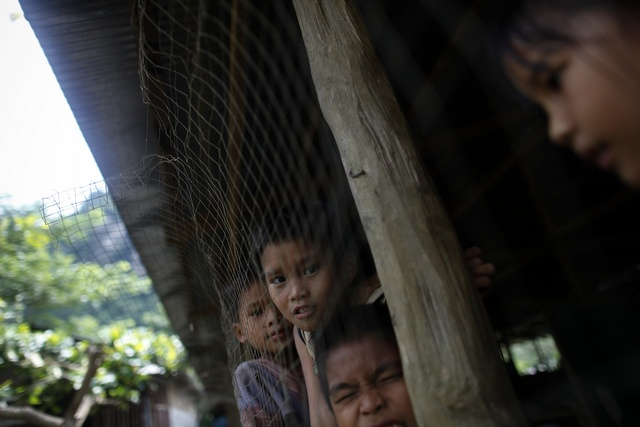 Burma's ethnic Karen children look from inside their school at the Mae La refugee camp outside Mae Sot near the Thailand-Burma border. (Reuters)