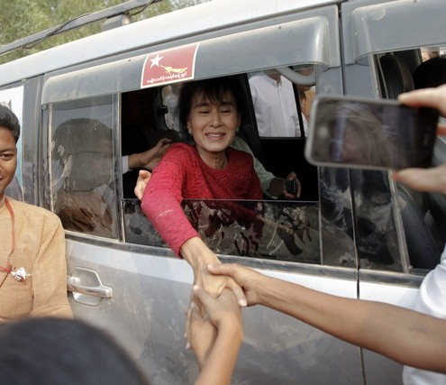Aung San Suu Kyi is greeted outside a polling station in Kawhmu township