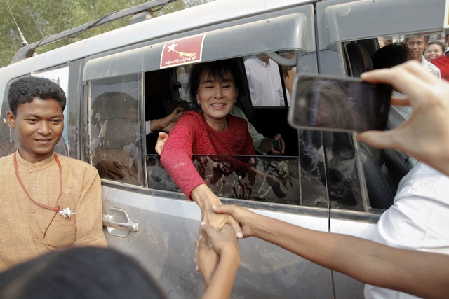 File photo of Aung San Suu Kyi being greeted outside a polling station in Kawhmu township in 2012. (PHOTO: Reuters)