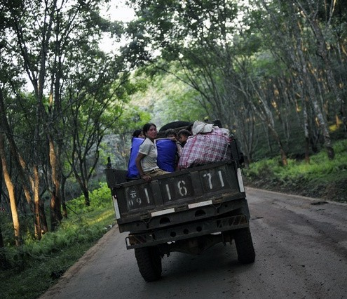 Refugees from Myanmar's Wa State ride on a vehicle to the China-Myanmar border gate at the border town of Mangka