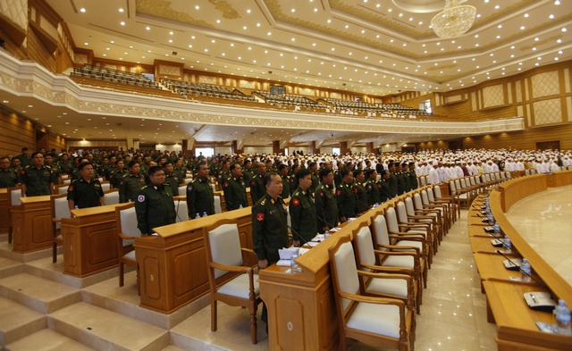 Members of parliament stand as the speaker of the Union Parliament arrives for a parliament meeting in Naypyidaw on 24 April 2012. (PHOTO: Reuters)