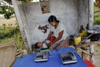 A woman and her child play at a public phone shop in Burma's new capital Naypyitaw on 1 March 2012. Burma has fewer phones per capita than any other country and probably the fewest Internet connections, and that has regional telecoms and IT companies licking their lips. (Reuters)