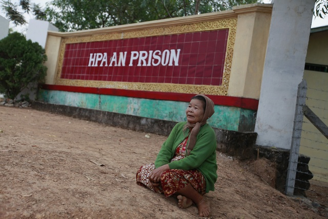 A family member of a prisoner awaits his release in front of Hpa-an prison on 13 January 2012.