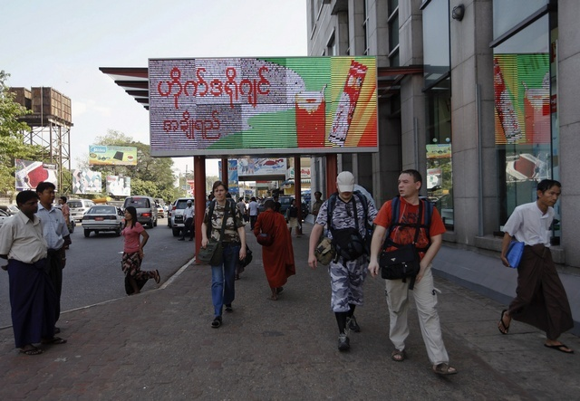 Tourists and a Buddhist monk walk in front of Sakura Tower in Rangoon (Reuters)