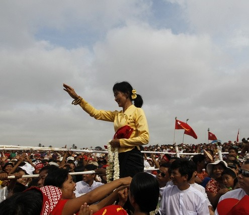 Myanmar pro-democracy leader Aung San Suu Kyi gestures at her supporters to sit down during an entertainment show at a ceremony to mark Myanmar's New Year Day in her constituency of Kawhmu township