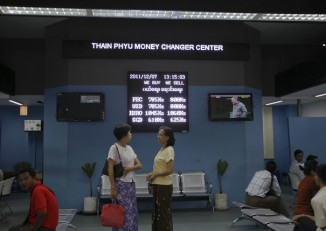 Women chat in front of an exchange rate board at a money changer in Rangoon on 7 December 2011. (Reuters)