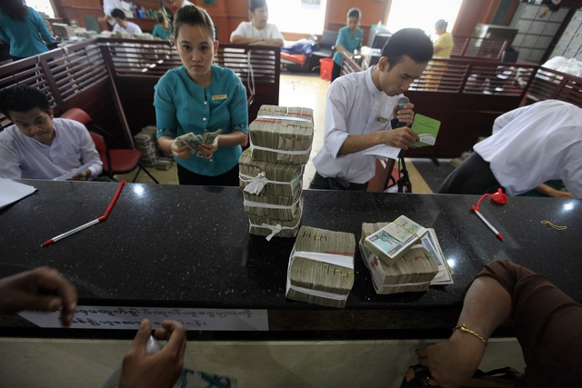 People exchange currency to Burmese kyat banknotes at the office of a local bank in Rangoon on 2 April 2012. (Reuters)