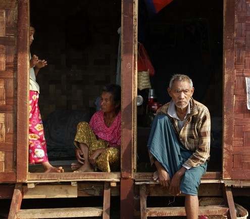 Ethnic Kachin people sit in the doorways of shelters at a temporary camp for people displaced by fighting between government troops and the Kachin Independence Army, or KIA, outside the city of Myitkyina