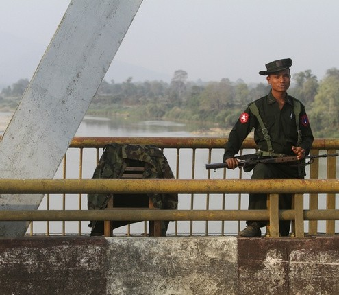 A Myanmar government soldier stands guard on Balaminhtin bridge over the Irrawaddy River near the city of Myitkyina