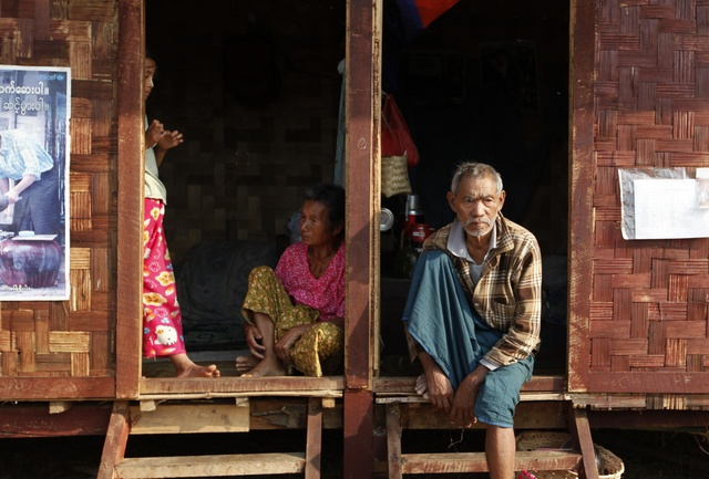 Ethnic Kachin people sit in the doorways of shelters at a temporary camp for people displaced by fighting between government troops and the Kachin Independence Army, or KIA, outside the city of Myitkyina in the north of the country on 22 February 2012. (Reuters)