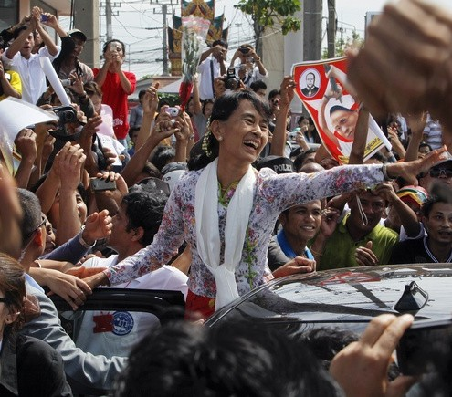 Myanmar&#039;s pro-democracy leader Aung San Suu Kyi greets migrant workers from Myanmar, as she visits them in Samut Sakhon province