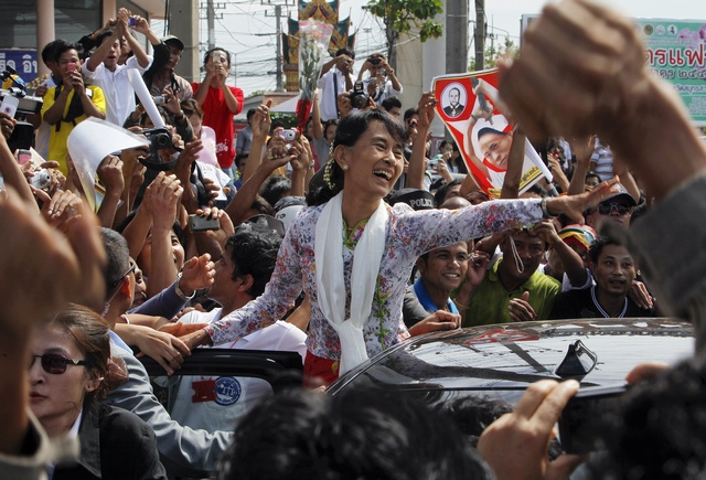 Aung San Suu Kyi greets migrant workers from Burma, as she visits them in Samut Sakhon province on 30 May 2012. (Reuters)