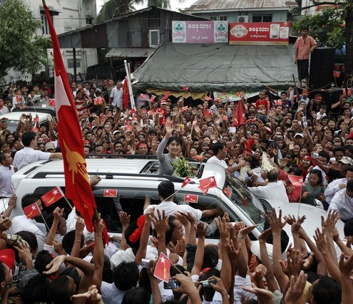 Aung San Suu Kyi waves to supporters as she arrives to attend the opening ceremony of her NLD party's branch office in Thar Kay Ta townwship in Yangon