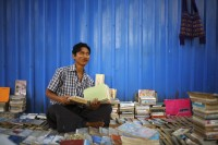 A street vendor is pictured as he sells second hand books on the streets of Rangoon on 6 March 2012. (Reuters)