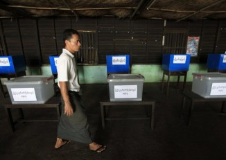 In this file photo, a Union Election Commission staffer walks past ballot boxes in Rangoon. (PHOTO: Reuters)
