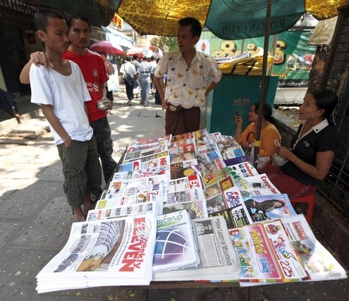 People stand at a newspaper stand with publications reporting on news about Myanmar's new parliament in central Yangon