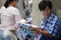 A man reads a newspaper with a picture of Burma's pro-democracy leader Aung San Suu Kyi hugging U.S. Secretary of State Hillary Clinton in central Rangoon on 3 December 2011. (Reuters)