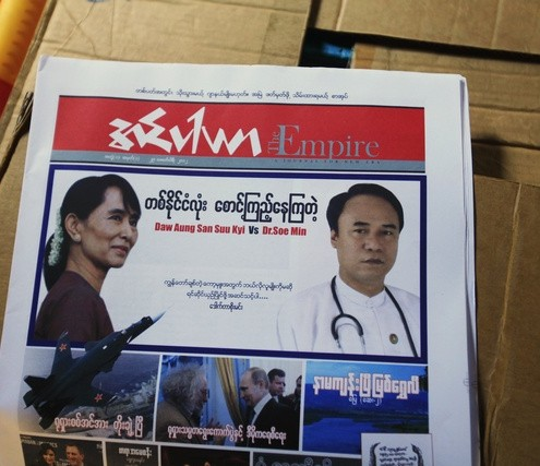 A newspaper with pictures of Soe Min and Aung San Suu Kyi is seen at Thartike village in Kawhmu township