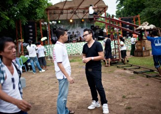 Thxa Soe chats with a friend yesterday on the set of a collaboration music video featuring several of Burma's hip-hop and rock stars. (Photo by Derek Stout)