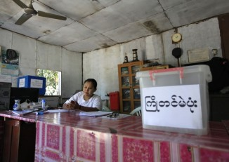 In this file photo, election commission staff sits near an advance ballot box at a ballot station at Mayangone township in Rangoon on 30 March 2012. (PHOTO: Reuters)