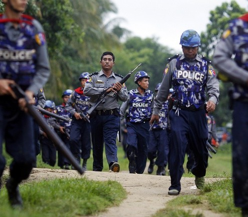 Policemen carry their weapons during fighting between Buddhist Rakhine and Muslim Rohingya communities in Sittwe