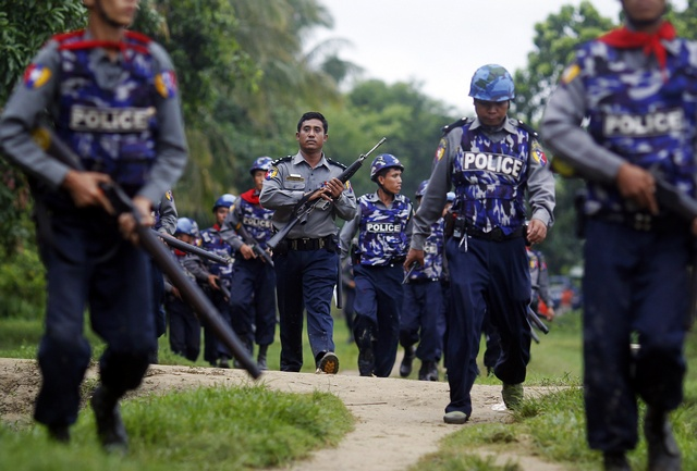 FILE PHOTO: Burmese policemen carry their weapons as they arrive in Sittwe on 10 June 2012. (Reuters)