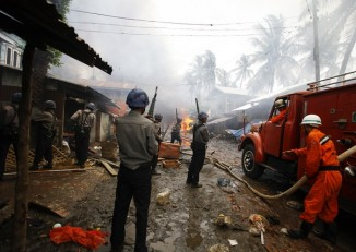 Policemen stand guard as firemen work to extinguish fire during fighting between Buddhist Arakanese and Muslim Rohingya communities in Sittwe on 10 June 2012. (PHOTO: Reuters)