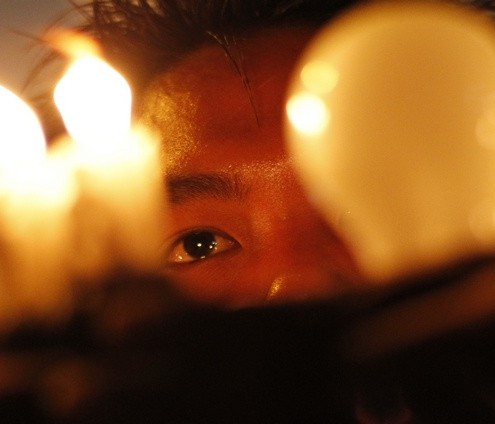 A man holds candles and an electrical bulb during a protest against the shortage of electricity near Sule Pagoda in central Yangon