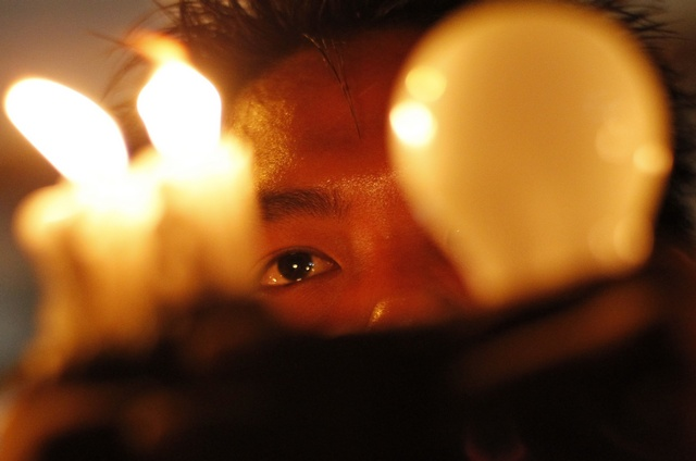 A man holds candles and an electrical bulb during a protest against the shortage of electricity near Sule Pagoda in central Rangoon in 2012. (Reuters)